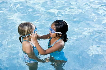 女の子は、7 年間、スイミング プールでの水泳のゴーグルを調整します。