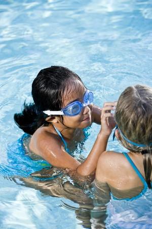 swim goggles: Ni�as, 7 a�os, el ajuste de las gafas de nataci�n en piscina  Foto de archivo