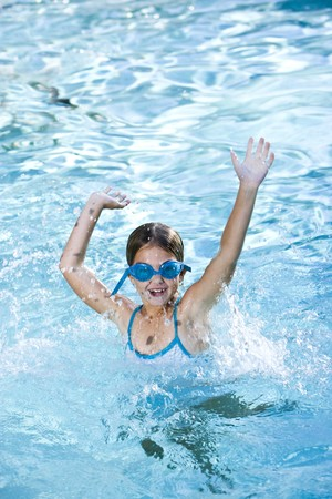 Girl, 7 years, wearing swim goggles, having fun splashing in pool