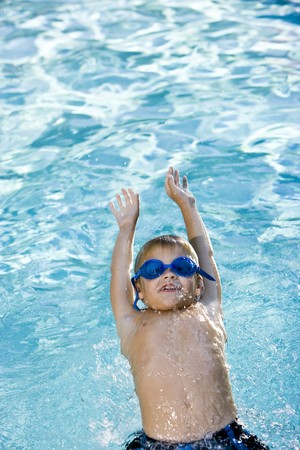 kids playing water: Happy boy wearing swim goggles, swimming on his back in pool, 7 years.