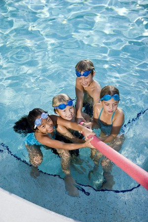 kids playing water: Multiracial friends tugging on pool toy in swimming pool, ages 7 to 9