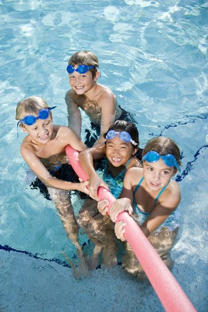 elementary kids: Multiracial friends tugging on pool toy in swimming pool, ages 7 to 9
