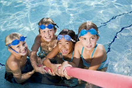 Multiracial friends tugging on pool toy in swimming pool, ages 7 to 9