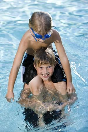 7 歳から 9 歳、肩の上に座ってプールで遊んでの男の子 写真素材