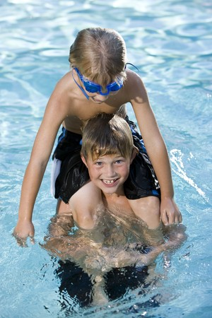 only boys: Boys, 7 and 9 years, playing in swimming pool, sitting on shoulders