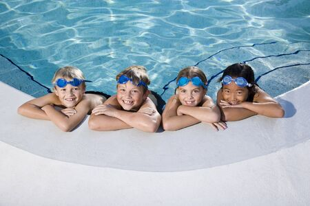 Multi-ethnic kids, relaxing in a row on side of swimming pool, ages 7 to 9 Stock Photo