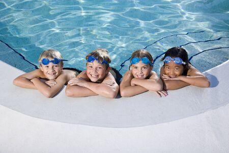 ni�os nadando: Ni�os multi�tnicos, relajantes en una fila del lado de la piscina, las edades de 7 a 9