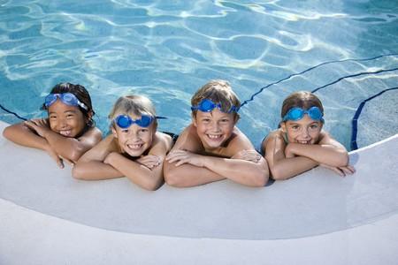 多民族の子供たちは、リラックスできるスイミング プールの側の行で年齢 7 に 9