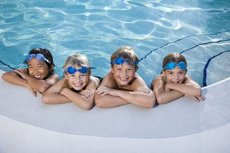 kids playing water: Multi-ethnic kids, relaxing in a row on side of swimming pool, ages 7 to 9 Stock Photo