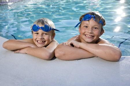 enfant maillot: Gar�ons heureuses accroch�e � c�t� de la piscine, 7 et 9 ans