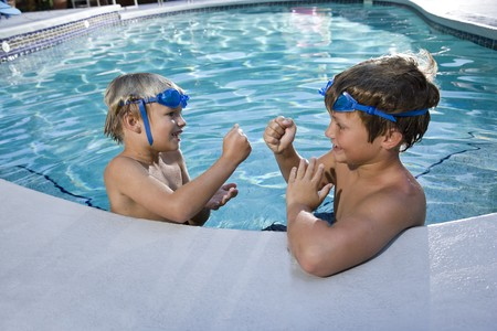 7 9 years: Two boys playing game of rock, scissors, paper in swimming pool, 7 and 9 years