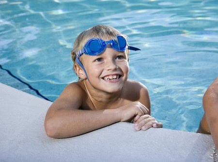 Happy boy with swim goggles looks up at side of swimming pool, 7 years