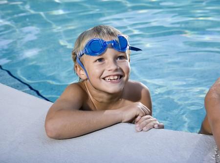 swim goggles: Ni�o feliz con chapuz�n gafas mira arriba al lado de la piscina, 7 a�os