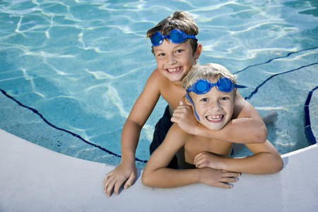 kids playing water: Portrait of happy boys at swimming pool