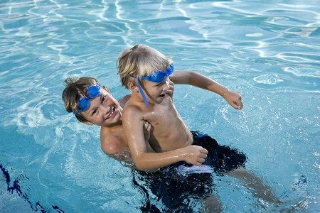 Boys will be boys - playing on side of swimming pool, 7 and 9 years Stock Photo - 8167856