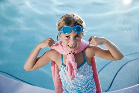 Girl, 7 years, playing by swimming pool in pretend superhero costume flexing muscles