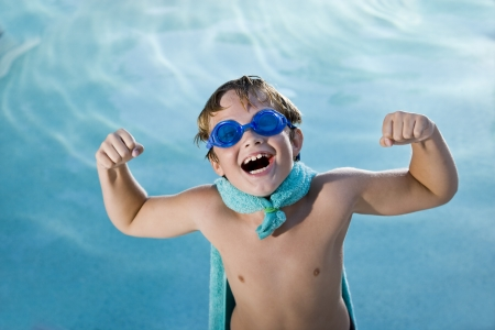 kids playing water: Boy, 9 years, playing by swimming pool in pretend superhero costume flexing muscles