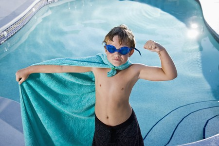 少年は、9 年間、ふりをするスーパー ヒーローの衣装の筋肉がうごめくのプールで遊ぶ