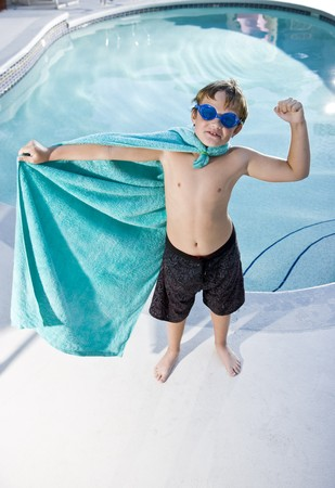 Boy, 9 years, playing by swimming pool in pretend superhero costume flexing muscles photo