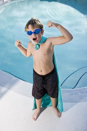 pretend: Boy, 9 years, playing by swimming pool in pretend superhero costume flexing muscles