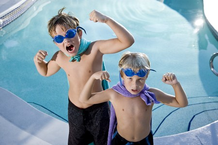 Boys, 7 and 9, playing superhero by swimming pool, flexing muscles