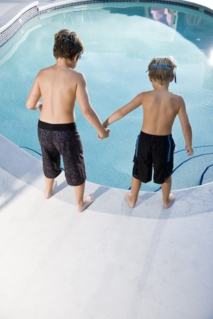 only boys: Boys, 7 and 9, looking down at water in swimming pool