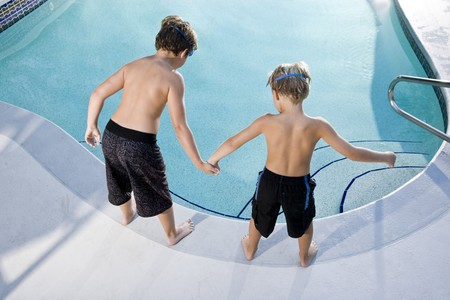 Boys, 7 and 9, looking down at water in swimming pool photo