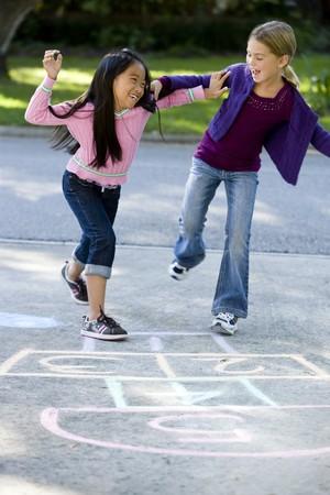 楽しい時を過す人種の友人の私道で石蹴りを再生 写真素材