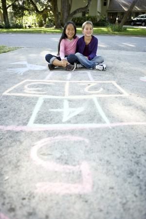 Two girls at home on driveway sitting in front of hopscotch board (7 years) photo