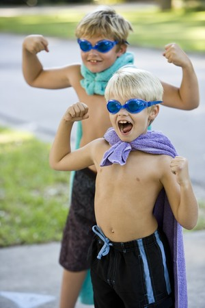pretend: Boys, 7 and 9 years, flexing muscles in superhero costumes, focus on boy shouting