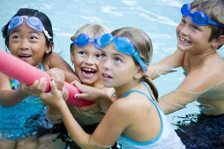 enfant maillot: Quatre enfants (7 � 9 ans) jouant de souque avec piscine toy, girl en avant-plan pas en focus Banque d'images