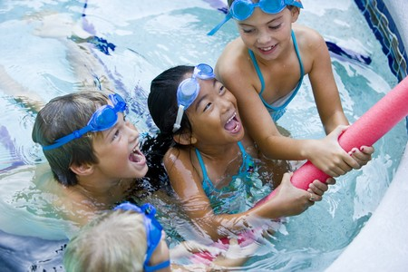 Four kids playing tug of war with pool toy, 7 to 9 years