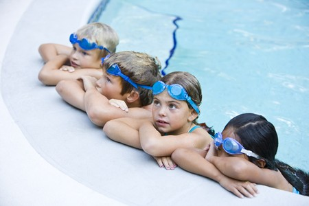 Multi-ethnic kids, resting in a row on side of swimming pool, ages 7 to 9.  Selective focus on Caucasian girl