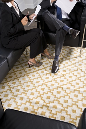 Cropped view of man and woman in business suits talking and reviewing report photo