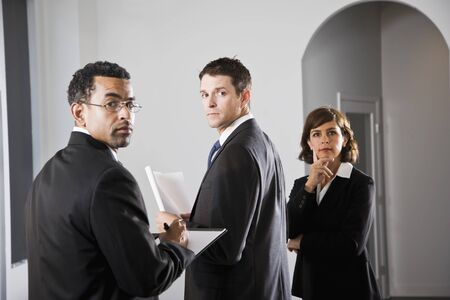 Diverse businesspeople meeting, looking over shoulder at viewer, focus on man in middle Stock Photo - 8338102