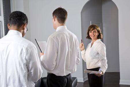 보고서를 읽는 동료와 회의에 서있는 사업가 스톡 콘텐츠