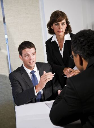 Mid-adult businessman and businesswoman meeting and negotiating with African American man photo