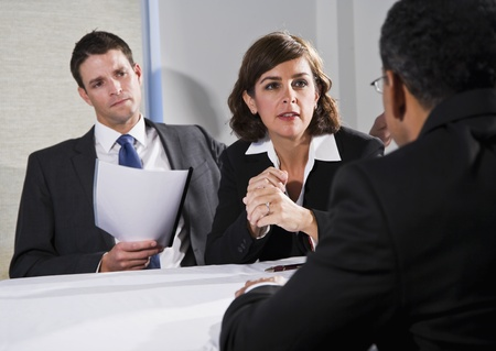 serious woman: Diverse business people conversing and negotiating, focus on businesswoman, 40s