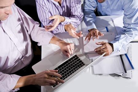 一緒にプロジェクトに取り組んで、話、身振りで示す、ラップトップ コンピューターの画面を見て 3 つのオフィス ワーカー