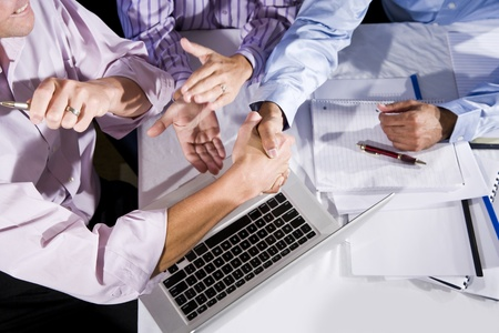 Three office workers working together on project, shaking hands and clapping.  Finished project or solved a problem. photo