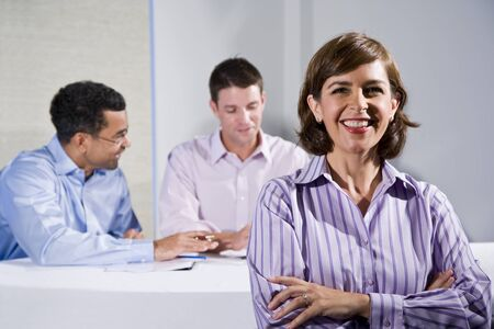 Confident woman (40s) in business meeting, businessmen talking in background