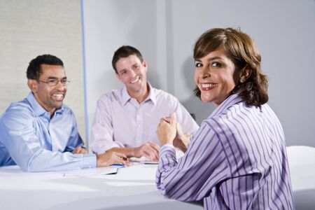 Confident woman (40s) in business meeting, businessmen across table photo