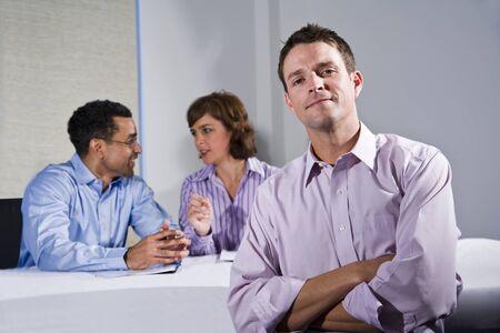 자신감이 남자 (30 대) 비즈니스 미팅, 배경에서 얘기하는 동료 스톡 콘텐츠