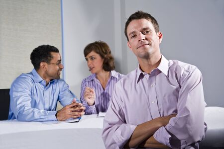 Confident man (30s) in business meeting, colleagues talking in background Stock Photo - 8338161