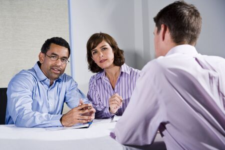 Multiracial business meeting in boardroom, sitting at a table, focus on people facing camera photo