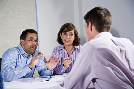 serious meeting: Multiracial business meeting in boardroom, sitting at a table Stock Photo