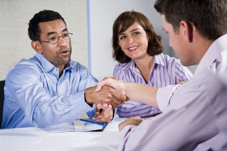 Multiracial business meeting in boardroom, shaking hands.  Focus on handshake Stock Photo - 8338142