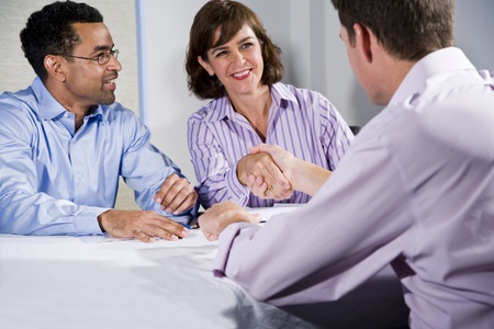 Multiracial business meeting in boardroom, shaking hands.  Shallow DOF, focus on handshake photo