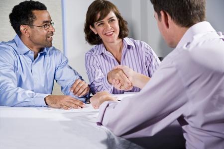 Multiracial business meeting in boardroom, shaking hands.  Shallow DOF, focus on handshake