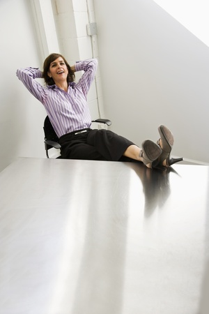 Businesswoman, 40s, smiling and relaxed with feet resting on office table
